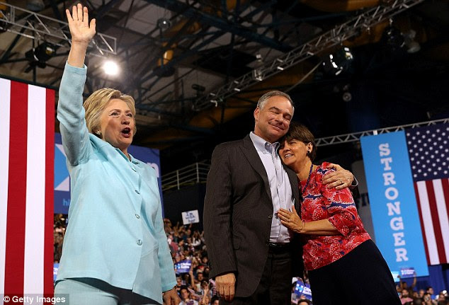 Clinton (L) greets supporters as Kaine hugs his wife Anne Holton during a campaign rally at Florida International University Panther Arena in Miami