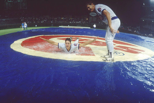 Cubs pitcher Greg Maddux slides on a wet infield tarp during a rain delay in the first night game at Wrigley Field on Aug. 8, 1988.  (Heinz Kluetmeier)