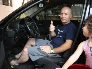 Observado por Lívia, Leandro mostra como dirige no carro adaptado (Foto: Felipe Truda/G1)