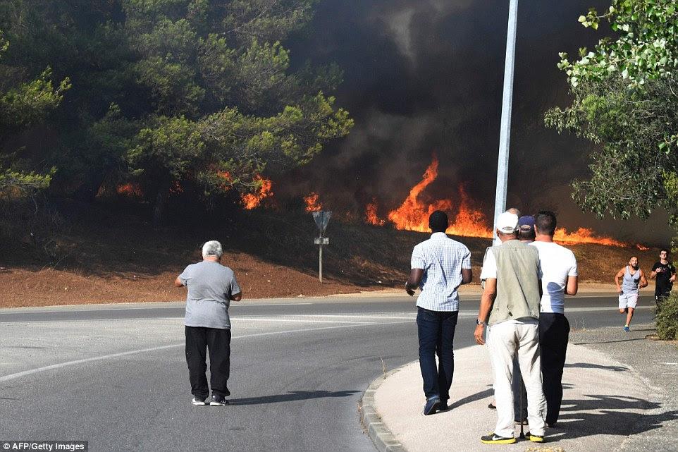 No sul da França, os moradores assistir as chamas queimando perto Vitrolles como dois homens (direita) vão correndo, quase inconscientes do perigo