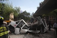 Firefighters work to remove a cement beam that fell from a bridge onto a public bus after an earthquake was felt in Mexico City Tuesday March 20, 2012. A strong 7.4-magnitude earthquake hit central and southern Mexico on Tuesday, collapsing at least 60 homes near the epicenter and a pedestrian bridge in the capital where people fled shaking office buildings. There were no passengers in the mini-bus and the driver suffered minor injuries, according to firefighters. (AP Photo/Alexandre Meneghini)