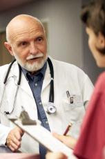 Photograph of a male doctor consulting with a female nurse