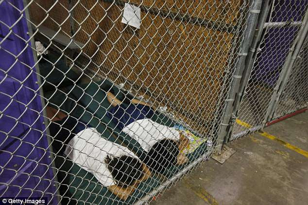 Two female detainees sleep in a holding cell at a center in Nogales, Arizona, on June 18, 2014. The center was set up to house unaccompanied child migrants who had crossed the border over the previous months