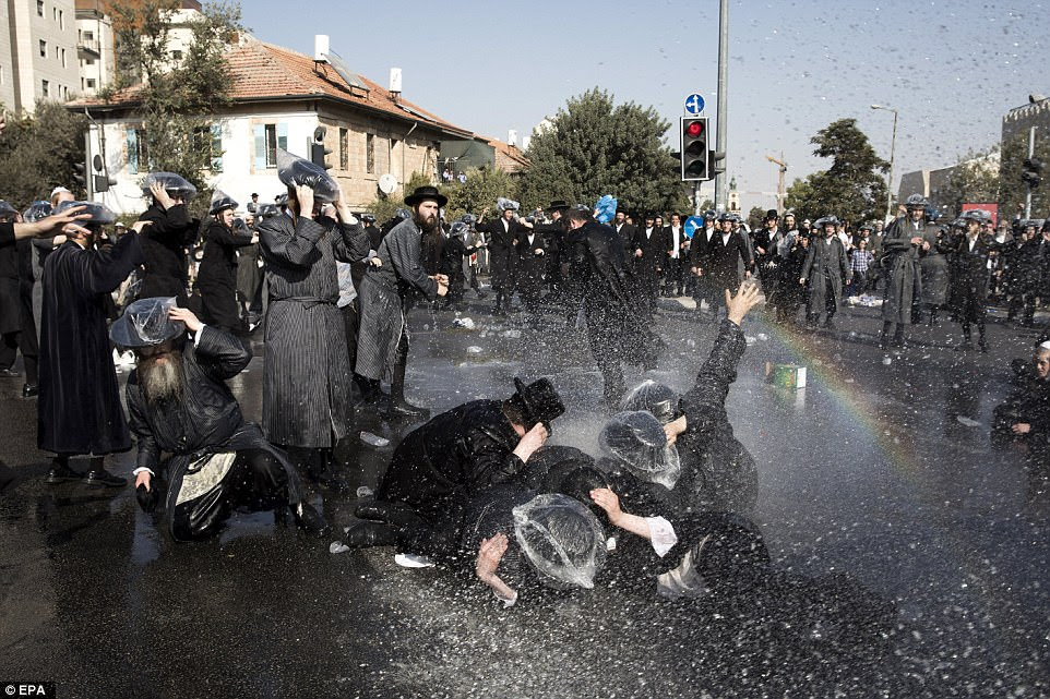 Israeli ultra-Orthodox Jewish men are sprayed with water during clashes with police at a protest against the detention of a member of their community who refuses to serve in the Israeli army