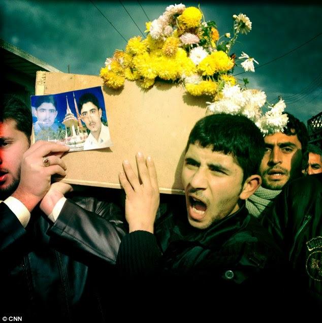 Morto: Membros da família carregam caixão Malik - seu irmão mais novo tem uma fotografia do homem morto