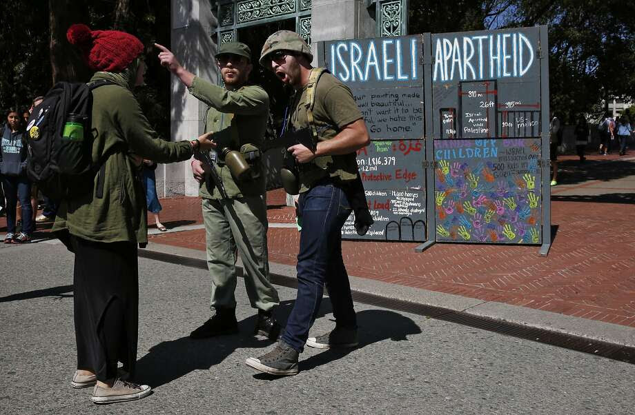 Protesters who preferred not to give their names role play as Israeli soldiers with a person role playing a Palestinian during a mock Israeli check-point demonstration near the Sather Gate on the University of California, Berkeley campus March 29, 2016 in Berkeley, Calif. The event was sponsored by Students for Justice in Palestine and was part of a week of events meant to raise awareness about the Palestinian situation. Photo: Leah Millis, The Chronicle