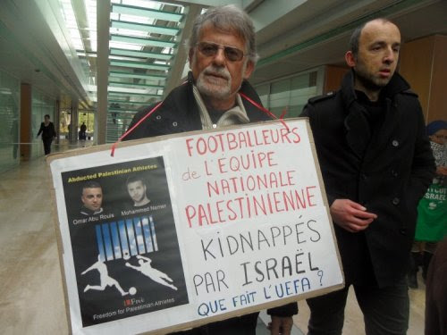 A protester's poster highlights Israel's detention of football players
