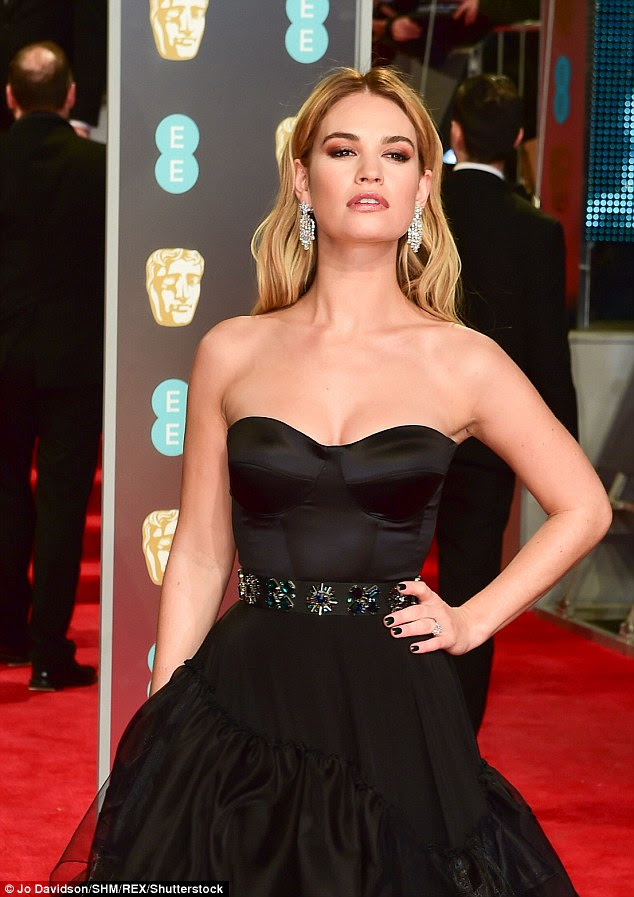 Sparkling: The blonde beauty, who began dating actor Matt Smith in 2014, looked positively regal in her sweetheart-necklined number from the British fashion house while her ring sparkled on the carpet