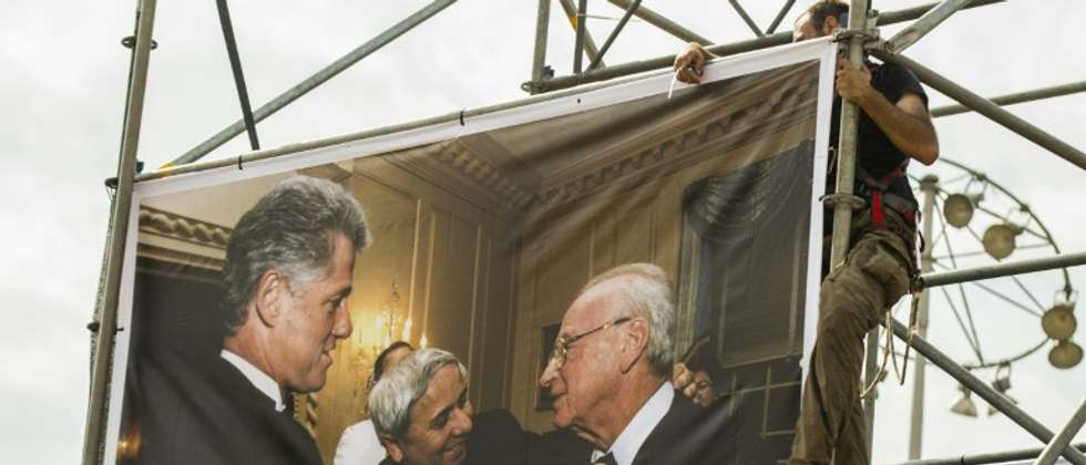 A worker hangs a picture taken by Israeli Government Press Office photographer Avi Ohayon showing former US president Bill Clinton arranging the tie of late Israeli prime minister Yitzhak Rabin, on October 26, 2015 in Tel Aviv ( Jack Guez (AFP) )