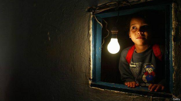 Un niño mira por una ventana con una bombilla encendida