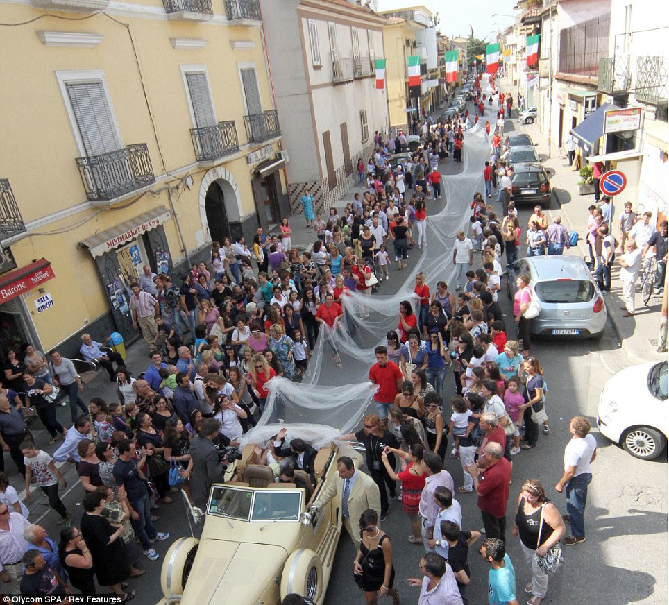 Here comes the bride: Elena is sitting in the vintage car as hundreds of people come out to help her carry the dress through the streets of Casal di Princice