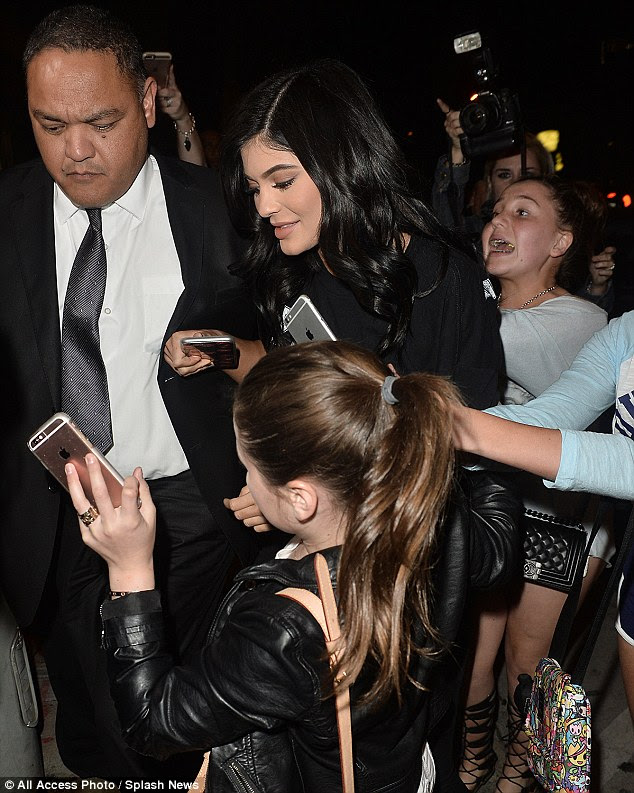 Busy: The teen was surrounded by young female fans but didn't stop to take any photos
