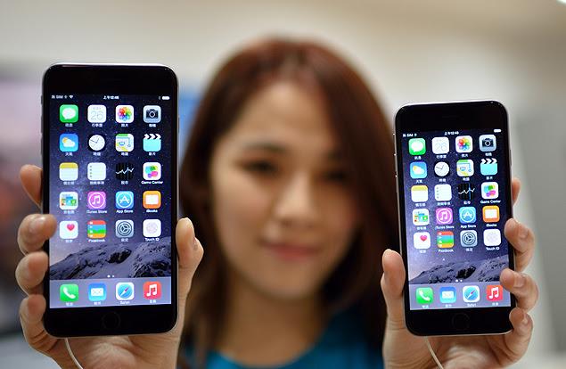 Funcionária de loja exibe o iPhone 6 e o iPhone 6 Plus (esq.) em loja de Taipé