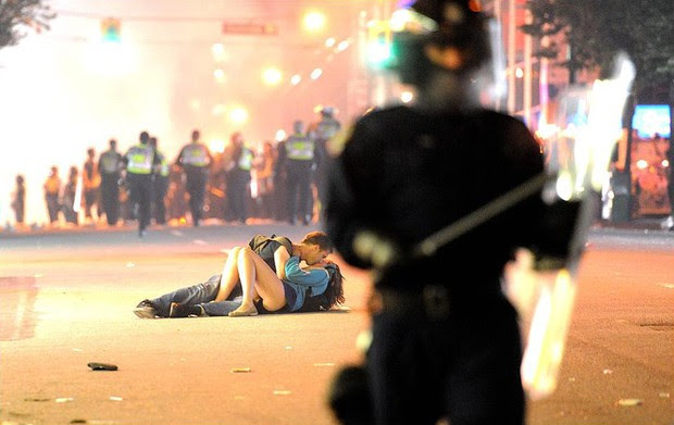 Moça se machuca em confusão com a polícia na final de hockey em Vancouver, Canadá, e namorado a acalma com um beijo, em 16 de junho (Foto: Getty Image)