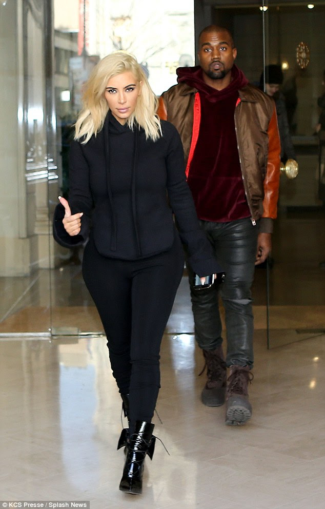 Not-so high fashion: Kim emerged from her hotel in Paris on Friday morning with husband Kanye, looking far less glamorous than she had the day before
