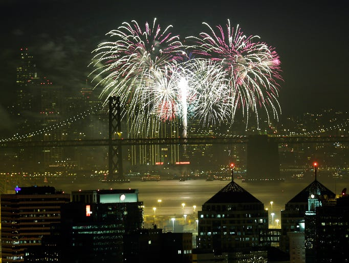 Fireworks fill the air in the bay over the Oakland and San Francisco skylines as part of New Year's Eve celebrations.