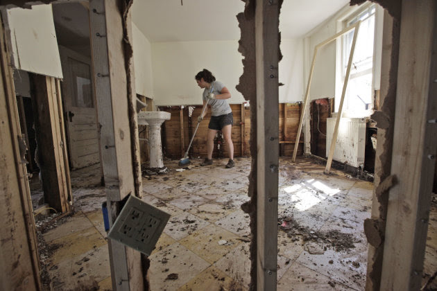 Meghan Morrow sweeps mud and debris from what is left of the Windham Spa, Tuesday, Aug. 30, 2011 in Windham, N.Y. Officials say more than a dozen towns in Vermont and at least three in New York are cu