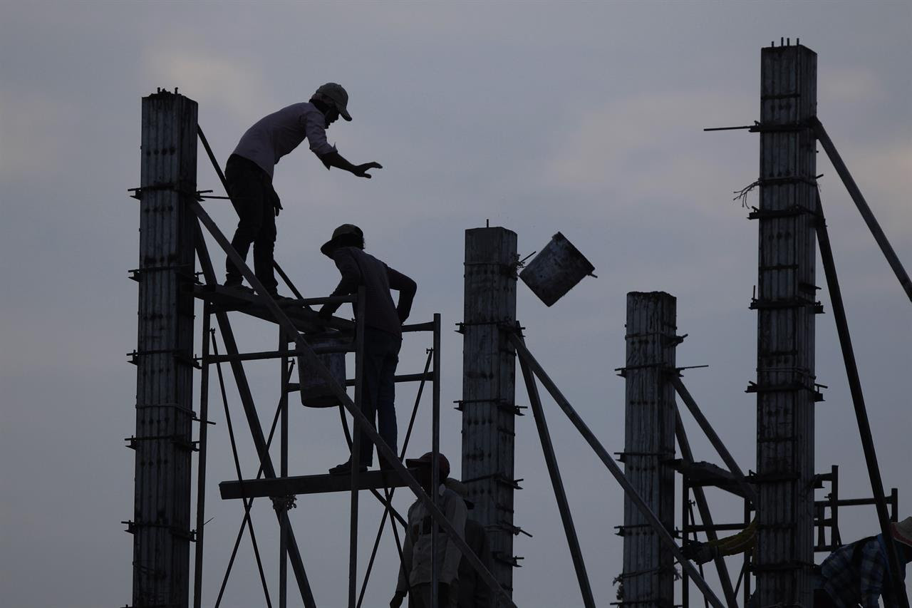 In this Tuesday, March 21, 2017 photo, workers on scaffolding are silhouetted at a building construction site near Phnom Penh, Cambodia.