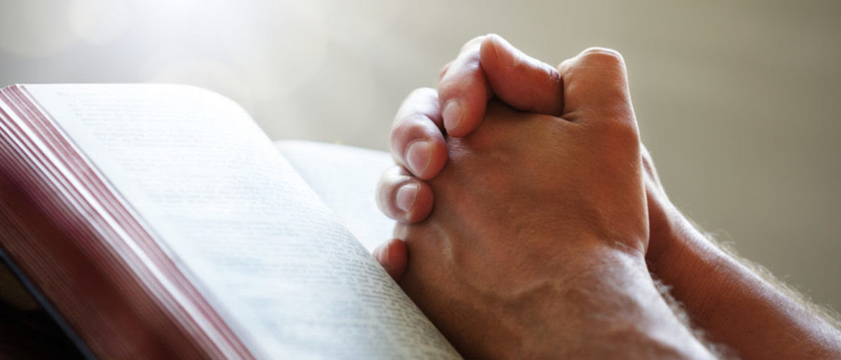 Hands folded in prayer on a Holy Bible in church concept for faith, spirtuality and religion (Brian A. Jackson/shutterstock_145450387)
