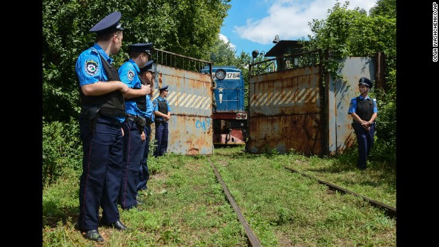 Police secure a refrigerated train loaded with bodies of passengers from Malaysia Airlines Flight 17 as it arrives in a Kharkiv, Ukraine, factory on Tuesday, July 22. The United States says a surface-to-air missile took down the Boeing 777 on Thursday, July 17, as it was flying over Ukraine from Amsterdam, Netherlands, to Kuala Lumpur, Malaysia, killing all 298 people aboard. Ukrainian officials have accused pro-Russian rebels of downing the jet, but Russia blames Ukraine's recent military operations against the rebels.