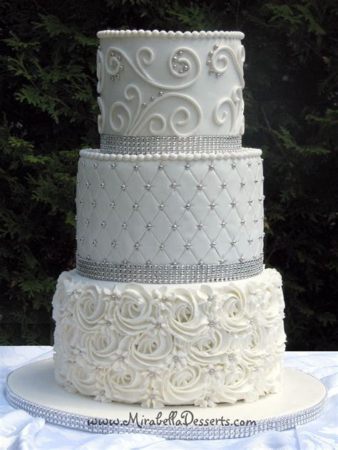 3 tier all white wedding cake decorated with buttercream