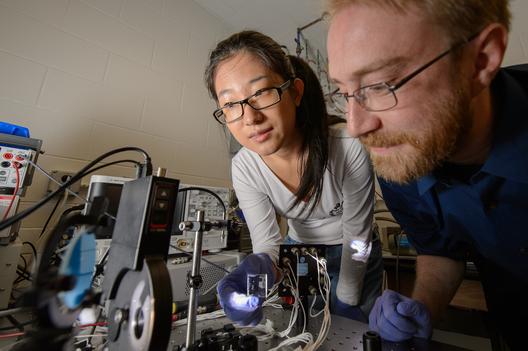 Yimu Zhao e Richard Lunt realizando um teste em laboratório do material. Imagem © G.L. Kohuth
