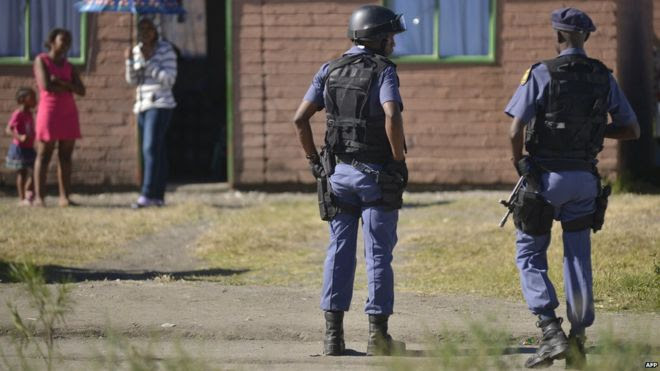 South African policemen patrol an area in Rustenburg on April 30, 2014