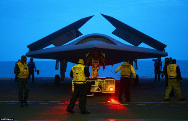 The Sun is about to rise as crew members prepare the X-47B UCAV for its first catapult launch from the flight deck of the USS George H.W. Bush, on May 14, 2013.