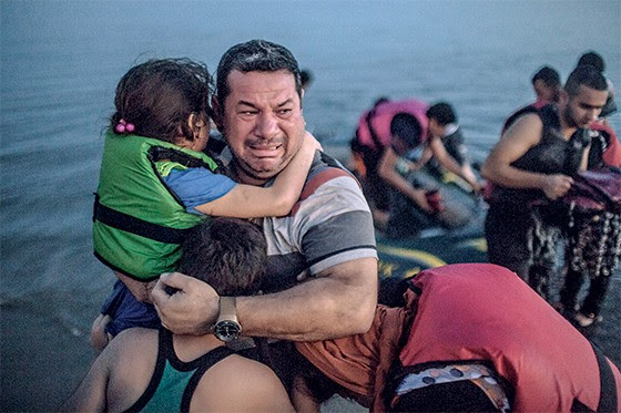 REJEIÇÃO 1. Um pai se agarra aos filhos em mais um barco de refugiados que aportou na Grécia   (Foto: Daniel Etter/The New York Times)