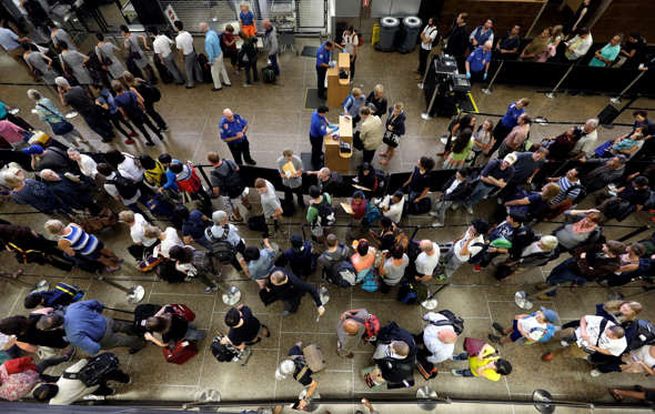 In this Tuesday, Aug. 11, 2015 photo, travelers wait in long security lines at Seattle-Tacoma International Airport, in Seattle.