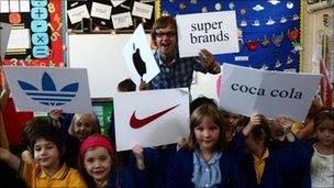Alex Riley and schoolchildren hold brand signs