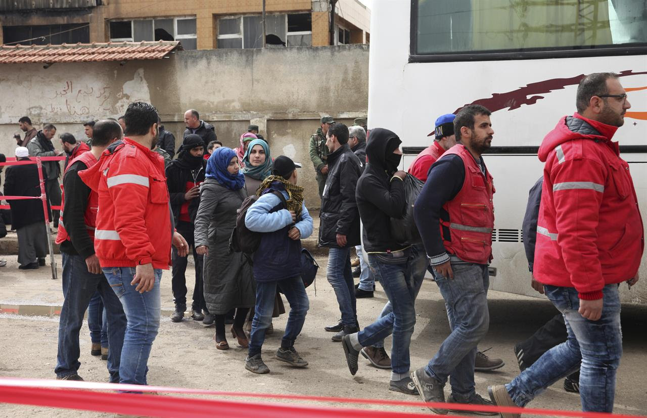 Gunmen and family members leave the al-Waer neighborhood bound for a town on the Turkish border, in Homs, Syria, Saturday, March 18, 2017. Scores of Syrian opposition fighters and their families have begun leaving al-Waer, the last rebel-held neighborhood in the central city of Homs as part of a Russian-backed evacuation deal signed earlier this week. The city was once known as the epicenter of the 2011 uprising against President Bashar Assad.