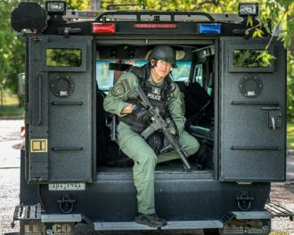A SWAT officer poses in the back of an armored vehicle (Jay Weenig)
