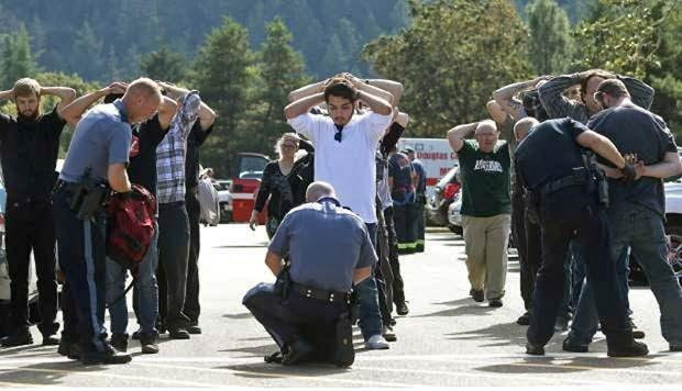 Estudantes são revistados ao sair da faculdade Umpqua, no Oregon, após atirador invadir e disparar (Foto: Mike Sullivan/Roseburg News-Review via AP)