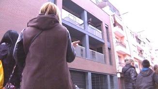 Els legítims propietaris discuteixen a peu de carrer amb un dels joves, que és al balcó del pis que ha ocupat