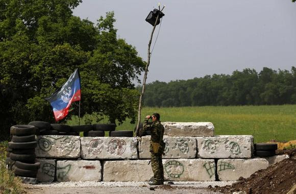 A pro-Russian militant surveys the area beyond a front line rebel position on the outskirts of the eastern Ukrainian town of Slaviansk May 19, 2014. REUTERS/Yannis Behrakis