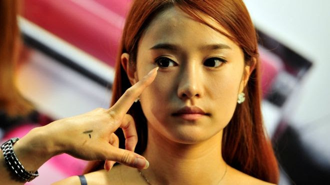 A South Korean model having her make-up applied