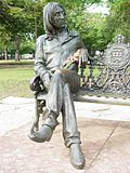 Statue of Lennon, bespectacled with long hair, on a park bench. There are red flowers in the statue's lap, and numerous trees are visible in the background.