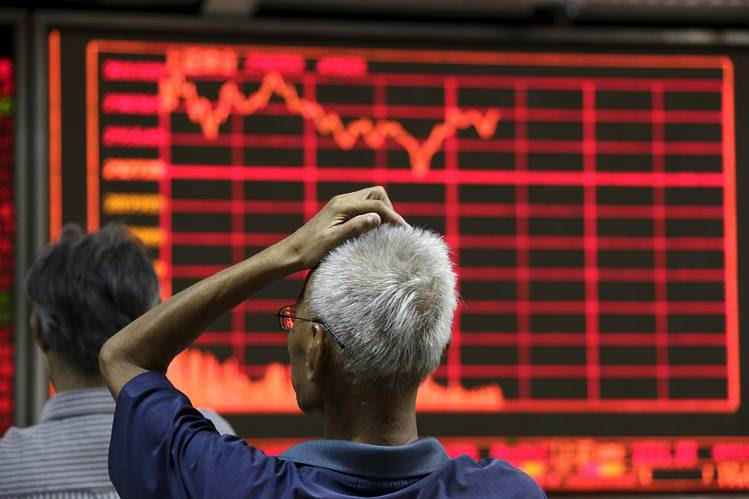 An investor looks at an electronic board showing stock information at a brokerage house in Beijing on Thursday.
