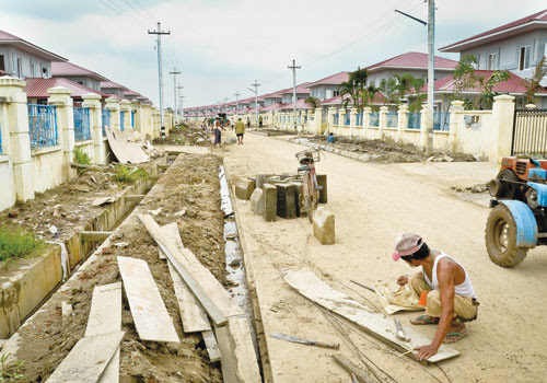 Workers perform roadworks at FMI Housing in Hlaing Tharyar township last week. Boothee / The Myanmar Times