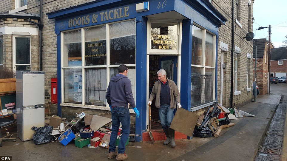 Following the floods: People clear up on Huntington Road in  York today. There is no suggestion they are connected to looting on the road