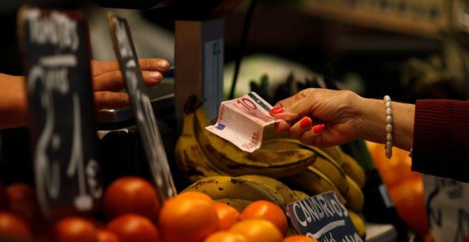 Un cliente paga con un billete de diez euros en un mercado en Málaga. / REUTERS