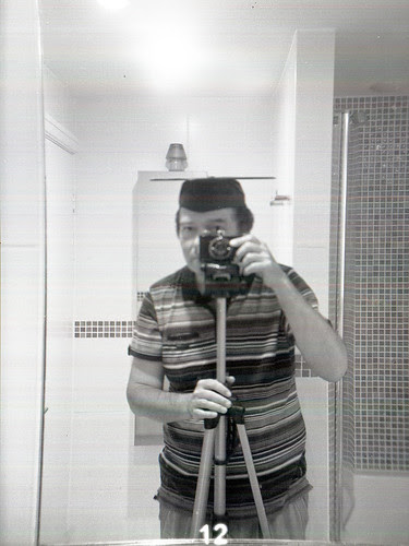 reflected self portrait with Falcon Miniature camera and mortar board by pho-Tony