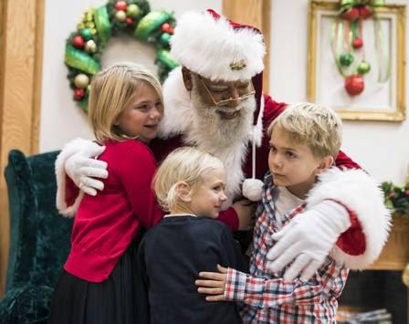 O papai noel é abraçado por crianças no shopping