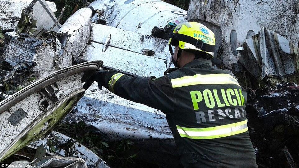 Um pesquisador da polícia olha através dos destroços do avião que os socorristas começaram a remover corpos do local esta manhã