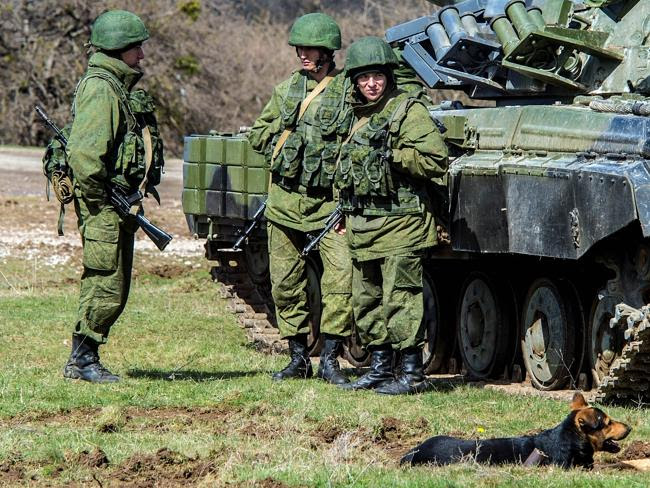 At the ready ... Russian soldiers stand near a tank outside a former Ukrainian military b