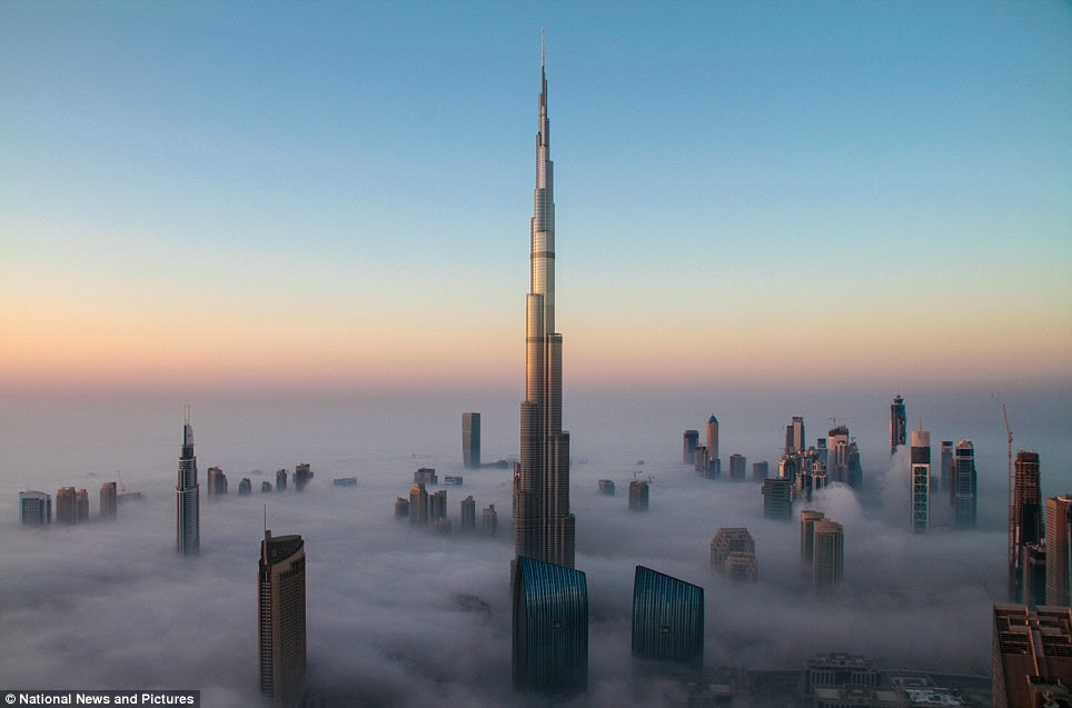 Stunning: The world's tallest building, the Burj Khalifa, juts above the fog in what looks like a science fiction scene