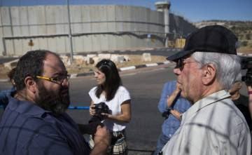 Vargas Llosa (d), junto a Yehuda Shaul ( Breaking the Silence), a la salida de Jerusalén, con el muro divisorio de fondo.