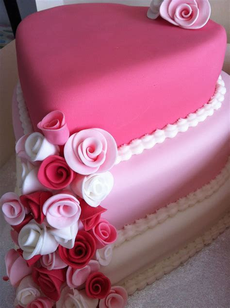 Three tiered pink heart shaped wedding cake adorned with