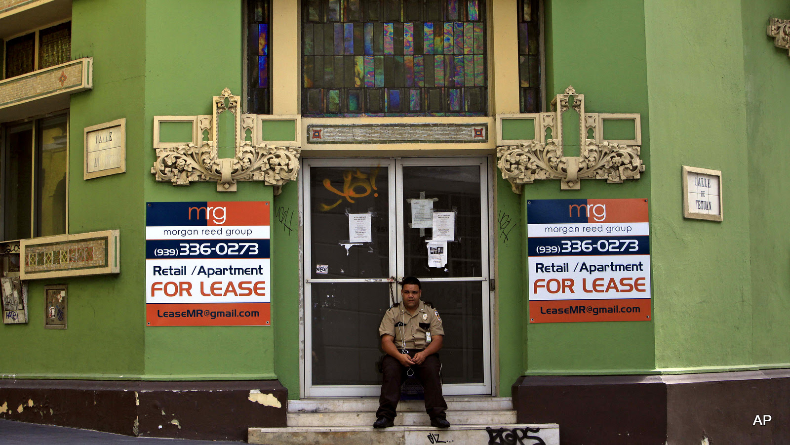A private security guard sits in front of a closed down business in the colonial district of Old San Juan, Puerto Rico